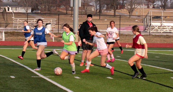 As head coach Jimmy Chapman looks on from their midst, prospective members of the 2021 Chillicothe High School soccer Lady Hornets work maneuvering the ball in traffic as a unit during practice Tuesday. CHS graduate Chapman was to serve his first year as head coach of the Lady Hornets last spring, but COVID-19 wiped it out, so he and the team are looking ahead eagerly to this year's scheduled season and home opener next Friday against Sedalia.