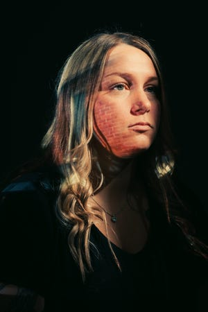 Mandie Matthews, a survivor of human trafficking, poses for a portrait taken by local photographer Nick Fancher. An image of a brick apartment complex, where she experienced abuse, is projected onto her face.