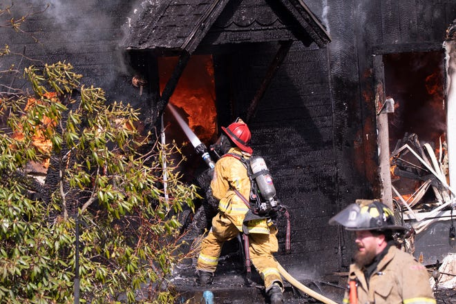 Firefighters battle a house fire on Stewart Street in Canisteo on Thursday.