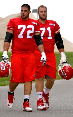 Kansas City Chiefs tackles Eric Fisher (72) and Mitchell Schwartz (71) walk to the field before the start of Kansas City Chiefs training camp in St. Joseph. The Chiefs released both Thursday morning in a cost-cutting move that will save the team approximately $18 million against the salary cap.