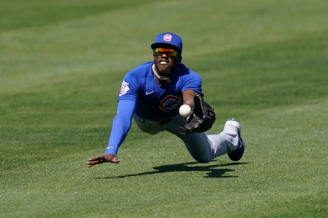 Chicago Cubs outfielder Cameron Maybin deflects a fly ball hit by San Francisco Giants catcher Buster Posey during the first inning of a spring training game Wednesday, in Scottsdale, Ariz.