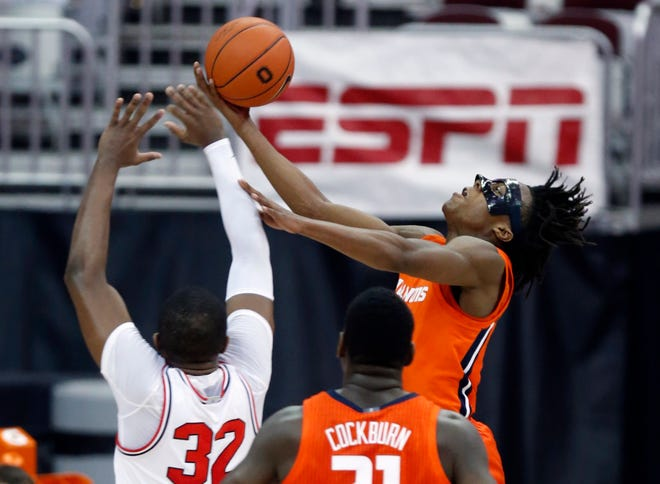 Illinois guard Ayo Dosunmu, right, goes up to shoot in front of teammate center Kofi Cockburn and Ohio State forward E.J. Liddell, left, during the first half of a game in Columbus, Ohio on Saturday, March 6.