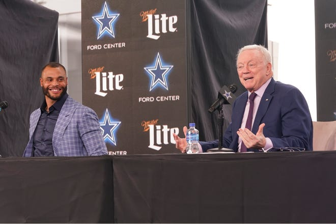Dallas Cowboys quarterback Dak Prescott, left, looks on and smiles as team owner Jerry Jones speaks during a news conference at the team's NFL football practice facility in Frisco on Wednesday. The Cowboys and Prescott have finally agreed on the richest contract in club history, two years after negotiations began with the star quarterback.