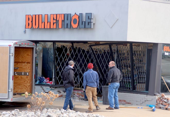 Crews worked Thursday, March 11, to repair the front of Bullet Hole Firearms and Training after suspects drove a car into the storefront early Thursday.