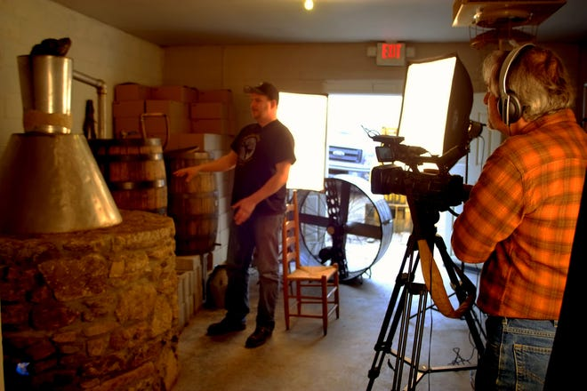 """A film still from """"Moonshining in the Mountains"""" shows Cody Bradford of Howling Moon Distillery in Asheville with the distillery's stills."""