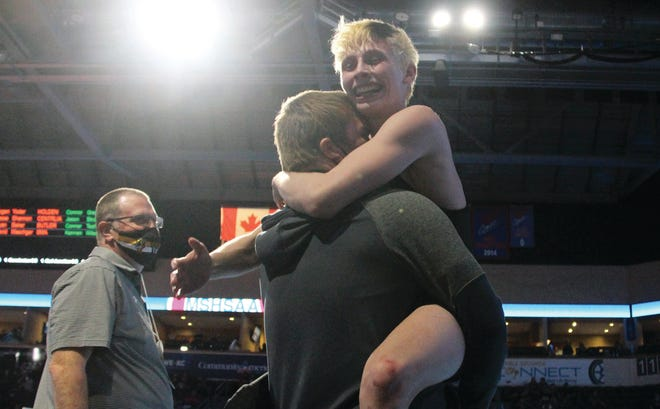 Versailles junior Kannen Wilson hugs his Assistant  Coach Brian Markway as Head Coach Shawn Brantley looks on in the MSHSAA Wrestling Championships on March 10 at Cable Dahmer Arena in Independence. Wilson had just won a consolation semifinal match that guaranteed him the first state medal of his career.