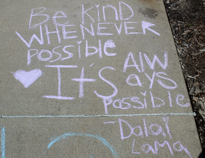 """A pink chalk message on a section of sidewalk outside Macomb City Hall reads, """" 'Be kind whenever possible. It's always possible' – Dalai Lama."""" A number of young Macomb residents chalked encouraging messages for passersby on Monday for the annual 309 Day of Kindness."""