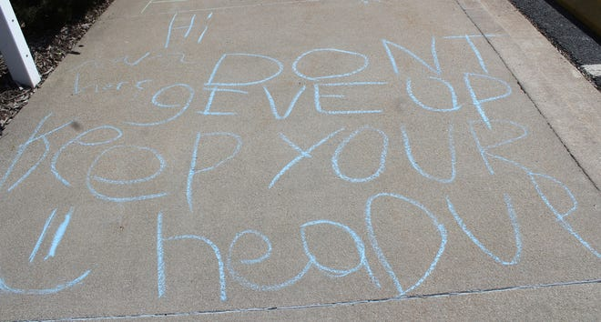 """A chalk message on a section of sidewalk outside Macomb City Hall reads, """"Hi. Don't give up. Keep your head up."""" A number of young Macomb residents chalked encouraging messages for passersby on Monday for the annual 309 Day of Kindness."""