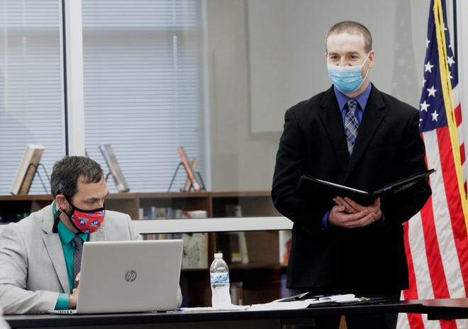 Ryan Eidson, business office manager for the school district, stands next to Moberly Public Schools Assistant Superintendent Dustin Fanning as he shared a financial report Tuesday evening during a March 9 school board meeting.