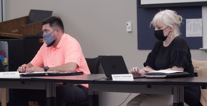 Moberly school board members Scott Head, left, and Heather Cleavinger listen to a report shared during a district business meeting held Tuesday, March 9.