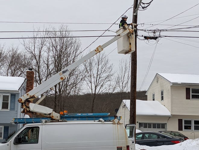 A Planet Networks employee installs fiber optics cables on a street in Newton Friday, Feb. 12, 2021.