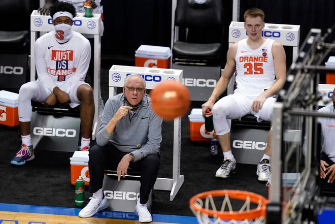 Syracuse head coach Jim Boeheim watches a shot as his son Buddy Boeheim (35) looks on during the second half of a second round of the Atlantic Coast Conference tournament Wednesday in Greensboro, N.C. Syracuse lost to Virginia on Thursday.