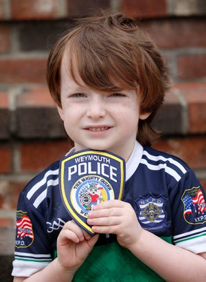 Quinn Waters, of Weymouth, who is fighting cancer again, holds a new patch that police are selling to help with his treatment costs on Thursday, March 11, 2021. Greg Derr/The Patriot Ledger
