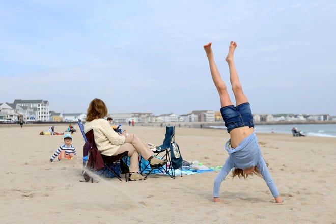 B. Raynor of Harrisville somersaults on Hampton Beach on an unusually warm morning last week.