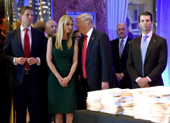 Donald Trump along with his children Eric, left, Ivanka and Donald Jr. arrive for a press conference at Trump Tower in New York, accompanied by Allen Weisselberg (second from right), chief financial officer of The Trump Organization. (Timothy A. Clary/AFP/Getty Images/TNS)