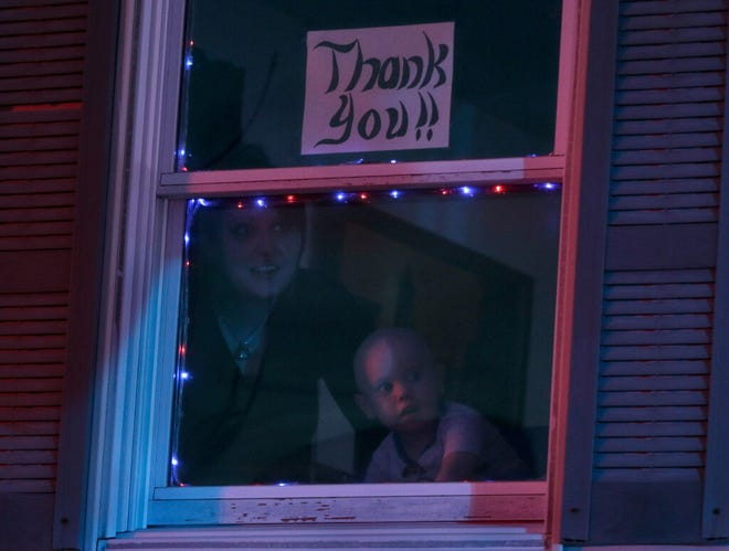 Rowan Shaw and his mother, Kendall, watch from their front window as a rolling river of police, fire and other first responders streams past their Warwick home earlier this month.