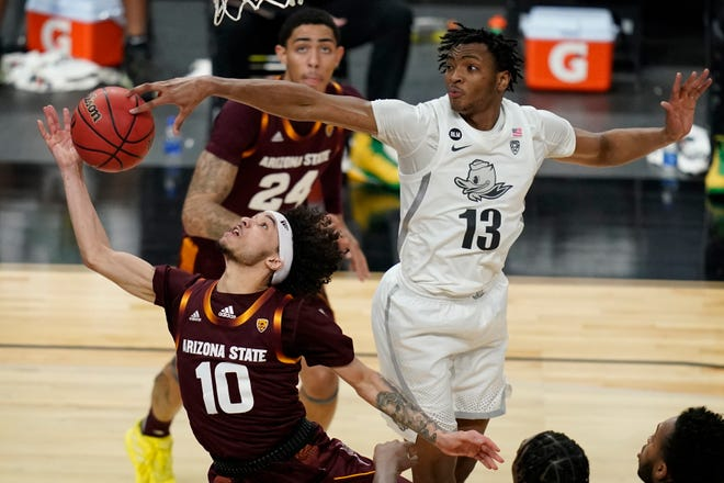 Oregon's Chandler Lawson (13) blocks the shot of Arizona State's Jaelen House during the first half of Thursday's quarterfinal game in the Pac-12 Tournament in Las Vegas.