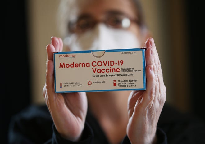 Registered nurse Lisa Parker, with Whitebird, holds a box of Moderna COVID-19 vaccine during a clinic put on my Whitebird at the WOW Hall in Eugene March 10, 2021.