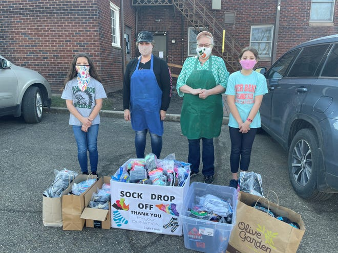 Layla Shinn, Alison Reed, Deb Charleston and Madi Hoopes (from left) pose with the socks Layla and Madi collected for the Alliance YWCA.