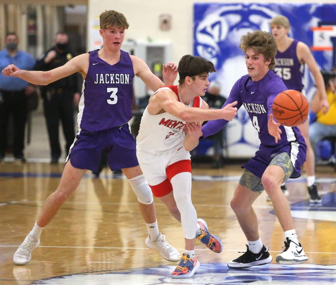 Kevin James (3) and Johnny Kulich (4) of Jackson guard Luke Chicone (center) of Mentor during the DI regional semifinal at Twinsburg on Wednesday, March 10, 2021.