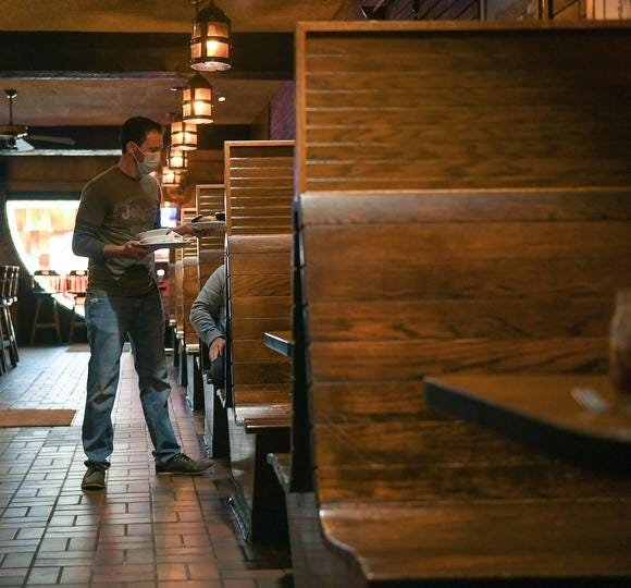 A server at John's Bar & Grille in Canton works down the line of redesigned booths during the restaurant's COVID-19 reopening in May 2020.