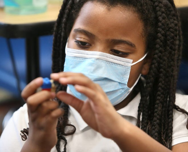 Second-grade student Asia Johnson studies a Lego at Regina Coeli School in Alliance where students participated in a University of Mount Union study that explored the effects of a face mask on children's health and learning.