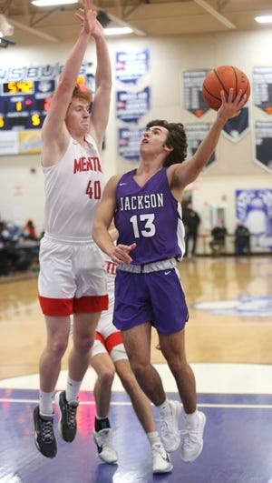 Michael Skeriotis (13) of Jackson goes to the basket while being guarded by Andrew Smith (40) of Mentor during the DI regional semifinal at Twinsburg on Wednesday, March 10, 2021.