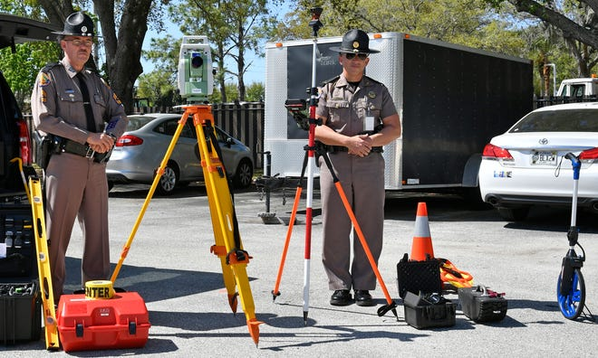 Sgt. Billy Pascoe, a 31-year veteran of the Florida Highway Patrol, and Lt. Greg Bueno, on right, public affairs officer for the FHP's Bradenton-based Troop F, stand with a digital survey system called the Leica Total Station, their new tool for investigating severe accidents.