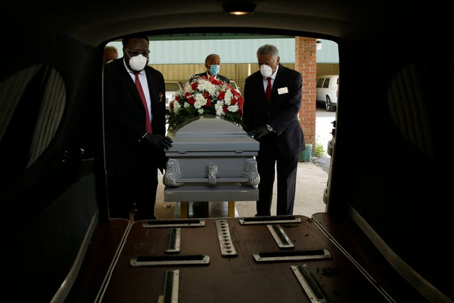 In this Saturday, April 18, 2020 photo, mortician Cordarial O. Holloway, foreground left, funeral director Robert L. Albritten, foreground right, place a casket into a hearse in Dawson, Ga. In a Feb. 25-March 1, 2021 poll conducted by The Associated Press-NORC Center for Public Affairs Research, about 1 in 5 Americans say they lost a relative or close friend to the coronavirus. (AP Photo/Brynn Anderson)