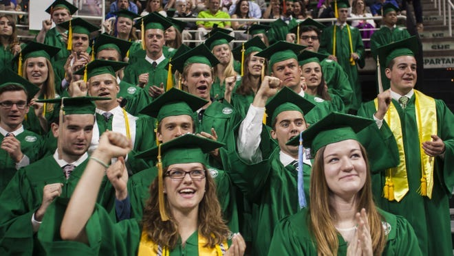 """Michigan State University graduates sing """"Victory for MSU"""" during spring commencement in May 2016."""