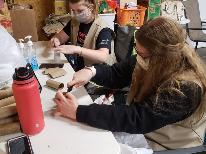 """Girl Scouts Savanna Walker, in 7th grade), left, and freshman Ashley VanWassenhove cut and shape toilet paper tubes for Troop 4444 Silver Service """"Save the Bees"""" project. The project began over a year ago but ran into some roadblocks including a pandemic. The group hopes to distribute their bee survival kits to interested residents in May."""