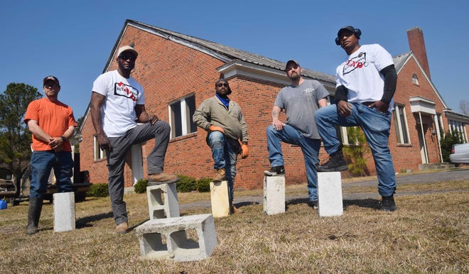 Corey Purdie, right, along with crew members Richard Whitfield, Paul Holt Jr., David Bright and Mack Jones are working on new homes for ex-inmates at an old school near Vanceboro.