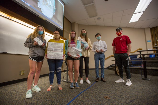 Several students in Washburn University professor Sangyoub Park's Social Class in the U.S. course show off the kind of diapers the class is collecting as part of a two-week diaper drive in the last half of March.