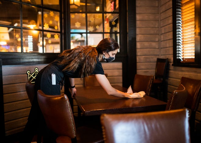 Solana Bethell cleans her tables between customers Tuesday at Jimmy's Tavern & Grill in Shrewsbury.