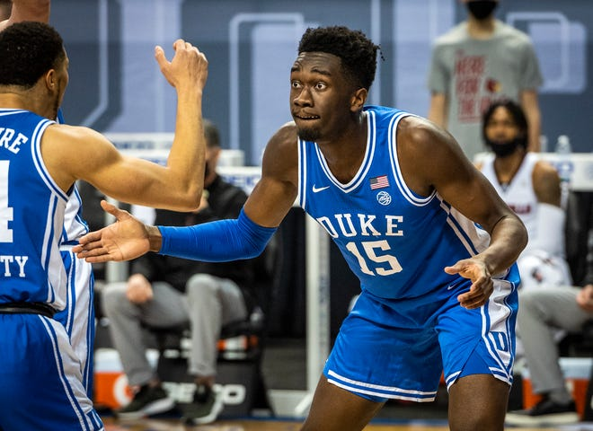 Duke's Mark Williams (15) celebrates after scoring a basket and drawing a foul with Jordan Goldwire (14) on Tuesday, March 10, 2021 in Greensboro, N.C. (Winston-Salem Journal/Andrew Dye) 031121-wsj-spt-duke