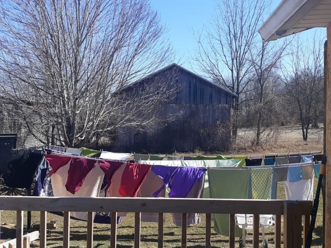 Lovina's daughter, Susan, enjoys the spring sunshine for hanging laundry out to dry.