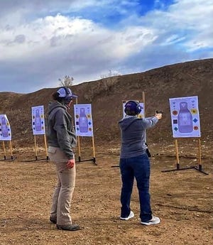 Cheri Armstong (left) of Prairie Sporting Goods in Pueblo West teaches a student proper handgun use during a class at Republic Shooting Range in Avondale.