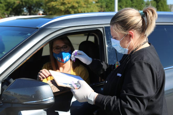 Susan Adams of Fort Smith answers a few questions Oct. 30 before receiving her drive-up flu shot from Clara Gable, LPN, at Mercy Convenient Care - 79th Street in Fort Smith.