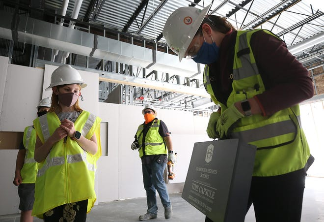 Edison Intermediate/Larson Middle School fourth-grader Evie Guse, 10, looks on as project engineer Colleen Cross shows a time capsule that was put inside the wall of Grandview Heights Schools' new grade 4-8 building March 9.