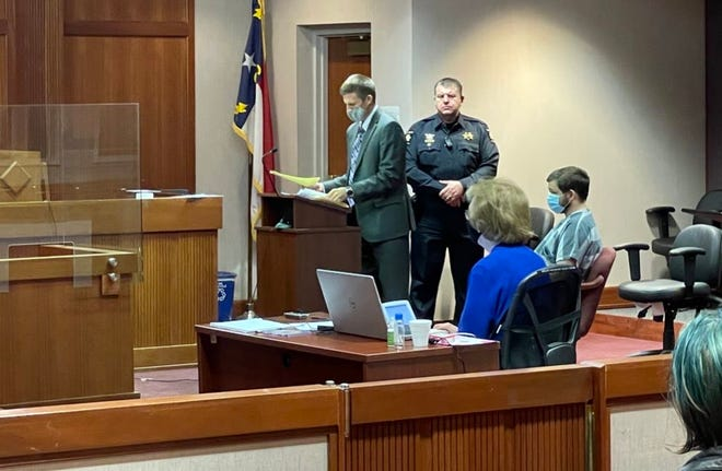 Jonathan Ponton, seated right, in Henderson County Superior Court March 11. Ponton pleaded guilty to a misdemeanor charge of assault on a female as part of a plea deal.
