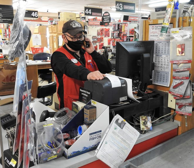 Tom Edwards, owner of Auer Ace Hardware, takes a phone call while checking out a customer. He said while his employees are above the proposed $15 federal minimum wage now, it could cause wages to go up for the store. That could result in higher prices and a reduction in services and store hours.