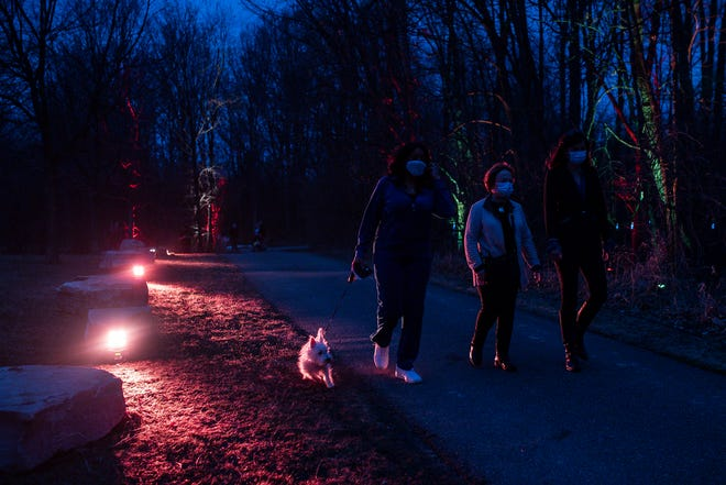 From left, Oakland County commissioners Janet Jackson, Eileen Kowall and Karen Joliat walk on a half-mile-long immersive and interactive light trail during the first day the Oakland Together COVID-19 Tribute Walk at Waterford Oaks County Park in Waterford Township, Wednesday, March 10, 2021.