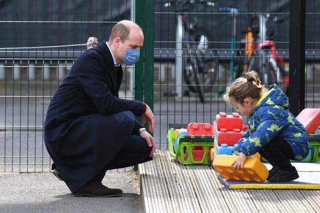 Pangeran William dari Inggris mengawasi seorang anak di taman bermain saat berkunjung ke sebuah sekolah di London timur, Kamis 11 Maret 2021.