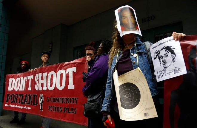 Dalam file foto 22 Maret 2017 ini, satu orang memakai bullseye dan topeng foto Quanice Hayes, yang ditembak dan dibunuh oleh seorang petugas polisi Portland, selama konferensi pers di Portland, Ore.