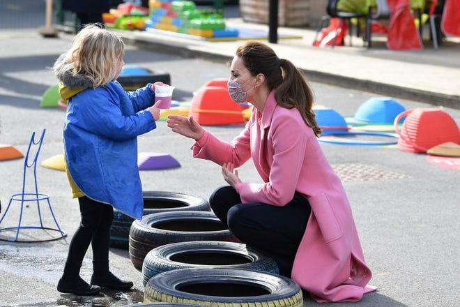 Kate, Duchess of Cambridge dari Inggris berbicara dengan seorang anak di taman bermain selama kunjungan dengan Pangeran William Kamis 11 Maret 2021.