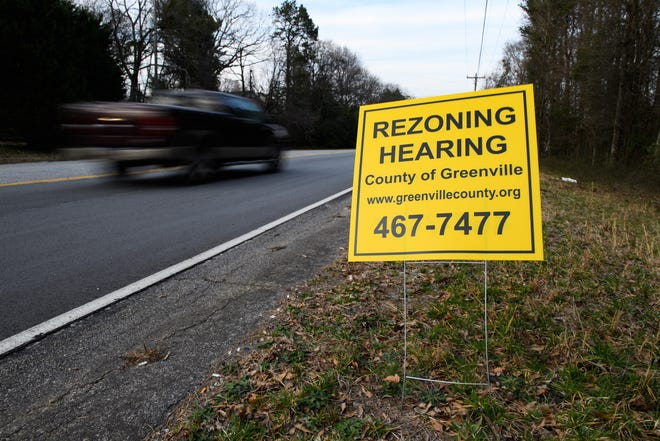 A motorist passes by a sign for a rezoning hearing at the site of a proposed housing development project at the intersection of Pelham Road and Hudson Road Wednesday, March 20, 2021.