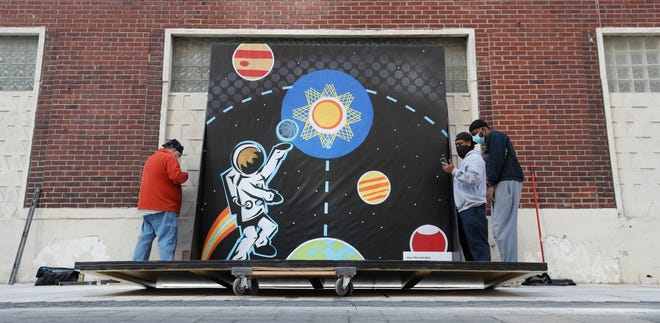 "From the Saphire Theatre Company, Andrew Hastings (from left), Gary Gee, Daniel A. Martin put together an art installation by artist Joy Hernandez on Wednesday, March 10, 2021, on Georgia St. in downtown Indianapolis. The piece is titled ""Shoot for the Stars, 2021."""