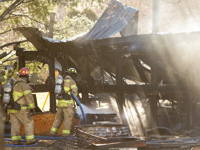 Firefighters from Hamburg, Putnam, Green Oak, Brighton and Northfield Townships fight a fire that destroyed a barn housing two vehicles and other utility items Thursday, March 11, 2021 on the Reichenbach property on Winans Lake Road in Hamburg Township.