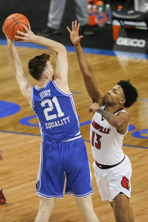 Mar 10, 2021; Greensboro, North Carolina, USA; Duke Blue Devils forward Matthew Hurt (21) shoots over Louisville Cardinals guard David Johnson (13) during the first half  in the second round of the 2021 ACC tournament at Greensboro Coliseum. Mandatory Credit: Nell Redmond-USA TODAY Sports