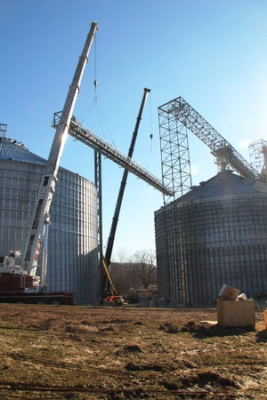 """""""Bridge Between"""" – Two heavy-duty cranes worked in concert to lift a 76,000 pound conveyor bridge to the tops of two 114-foot high grain bins at Centerra Co-Op's Mansfield grain facility."""